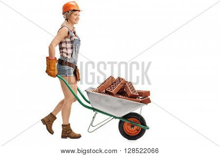Profile shot of a young female construction worker pushing a wheelbarrow full of bricks isolated on white background