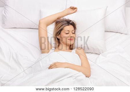 Joyful young woman sleeping on a comfortable bed and smiling