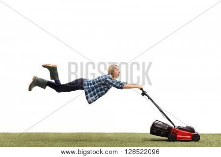 Woman mowing a lawn and being pulled by the lawnmower isolated on white background