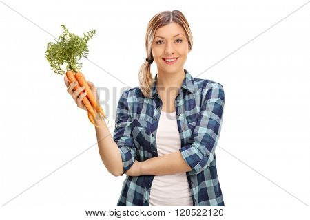 Young woman holding a bunch of carrots and looking at the camera isolated on white background