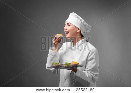 Professional chef tasting fruit tarts on grey background.