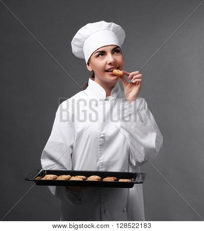 Professional chef tasting  cookie from a tray on grey background.