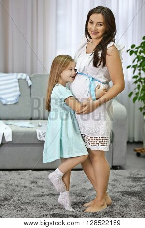 Happy pregnant woman and her child hugging