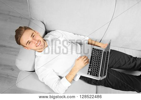 Young businessman working with laptop on sofa