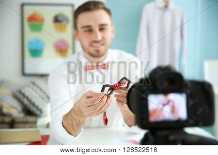 Young male blogger with tie bow recording video at home