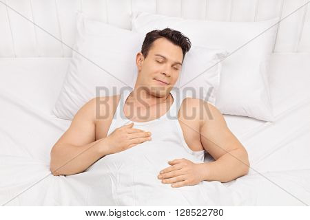 Happy young man sleeping on a comfortable bed and dreaming