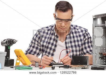 Male PC technician repairing a desktop computer and measuring electrical resistance isolated on white background