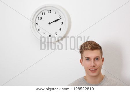 Young handsome man and clock on wall