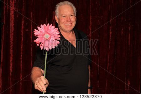 A handsome middle aged man smells fake flowers while posing in a photo booth as he has his picture taken.