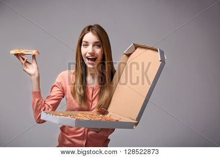 Happy young woman holding hot pizza in box on grey background
