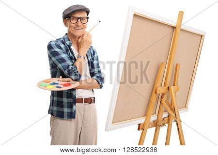 Senior artist holding a paintbrush and posing next to a canvas isolated on white background