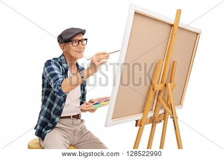 Senior artist painting on a canvas with a paintbrush isolated on white background