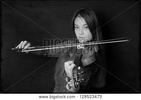 young asian woman playing violin in black and white