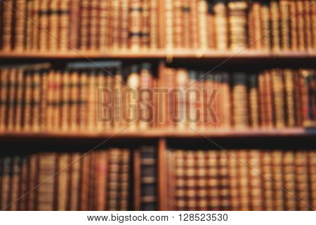 Blurred background of old books on shelves in library. Vintage books, retro style.