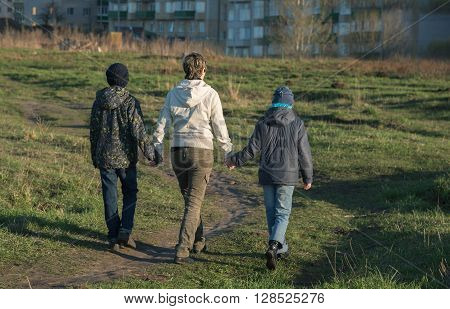 Mother, son and daughter walk in the park in the spring