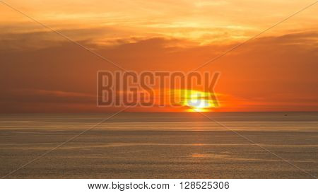 Blur beautiful soft orange sky above the sea. Sunset in background. Abstract orange sky. Dramatic golden sky at the sunset background.
