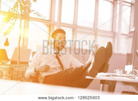 Relaxed young businessman first at workplace at early morning, listening music on headphones at modern startup office.  Sunrise sun flare in background