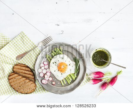 Healthy breakfast set. Fried egg with green asparagus, radishes, green sauce and bread on vintage metal plate over white wooden backdrop, top view, copy space