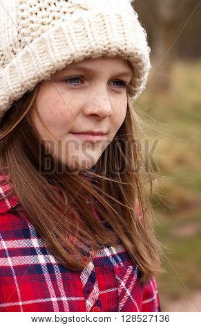 Portrait of a pretty young girl with freckles looking into the distance