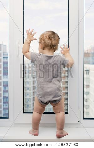 Baby boy in gray clothes looking at window