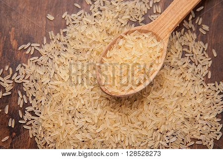 uncooked brown rice with spoon and woody background