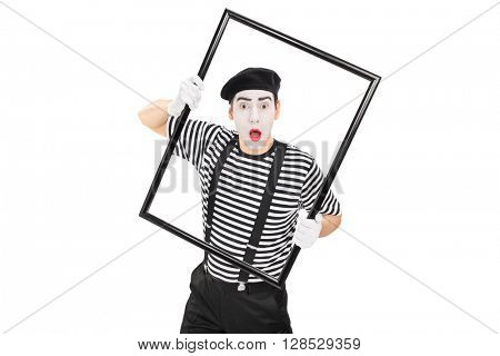 Young mime artist performing with a large black picture frame isolated on white background