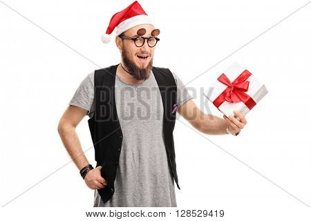 Man with hipster glasses and Santa hat holding a present isolated on white background