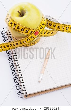 Fresh And Green Organic Apple With Metering Tape And Notebook On White