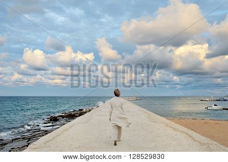 woman walking on the quay on a windy day Ostuni Apulia mediterranean Italy