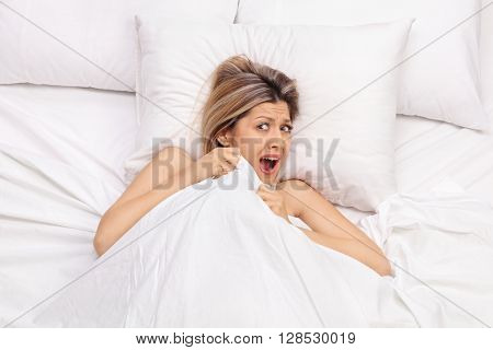 Scared young woman lying in bed covered with a blanket and screaming