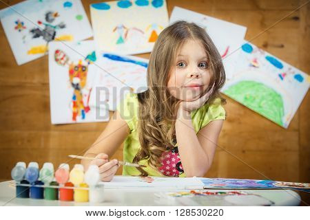 The little girl preschool child draws in an album multi-colored paints. Children's drawings.
