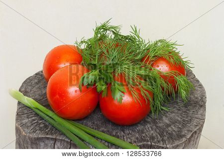 tomatoes on the stump with greens on a white background