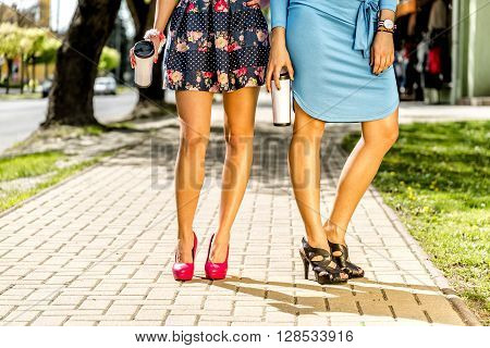 Women's leg with coffee in the city at summer.