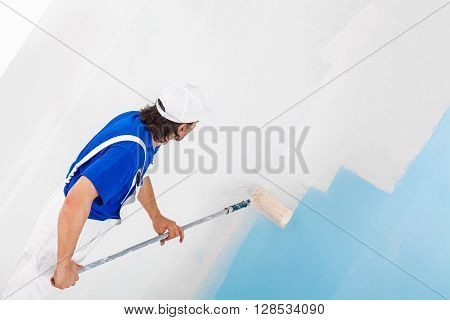 Painter Painting A Wall With Paint Roller