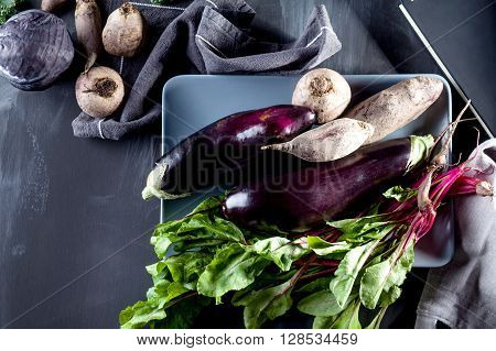 Beetroots aubergines and beet leaves on the plate with recipe notebook on the side top view