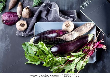 Beetroots aubergines and beet leaves on the plate with black notebook and cloth on the side top view