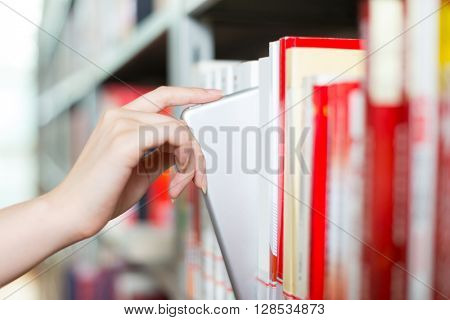 young beautiful asian girl university student with tablet in library