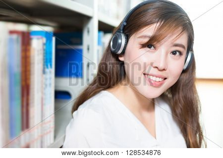 young beautiful asian girl university student with headset in library
