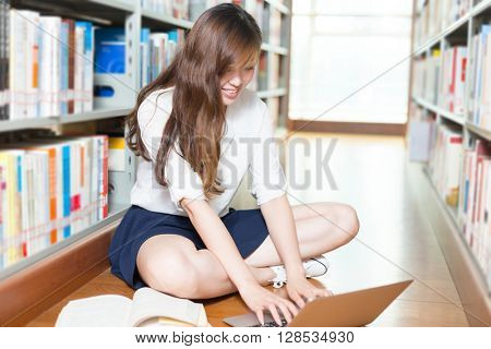 young beautiful asian girl university student with laptop in library