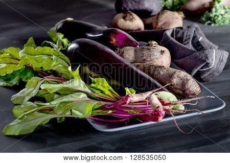 Beetroots aubergines and beet leaves on the plate on blackboard