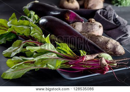Beetroots aubergines and beet leaves on the plate with dark cloth