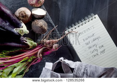 Beetroots aubergines black turnips and beet leaves with apron and notebook on the side top view