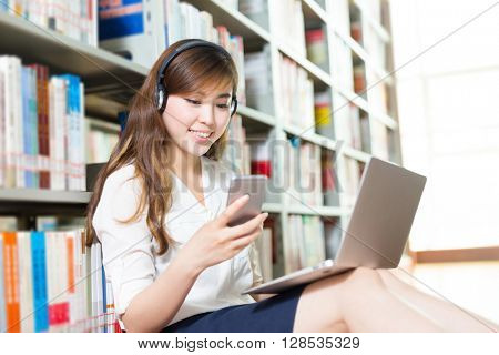 young beautiful asian girl university student with laptop and mobile phone in library