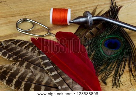Fishing fly tying materials and tools on a wooden table