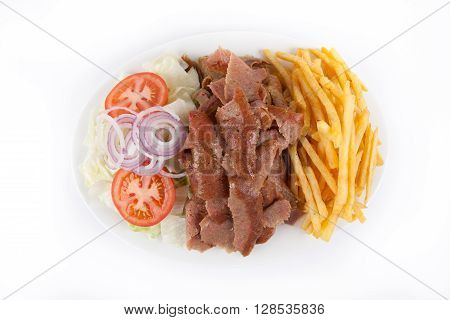 Kebab with french fries and salad on a plate