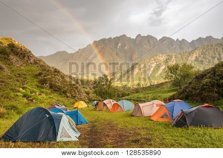 Double rainbow at campsite in mountains background