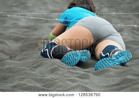 Crawling,passing under a barbed wire obstacles during extreme obstacle race