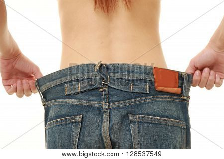 woman in large pant after losing weight on white background