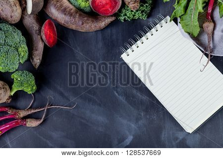 Beetroots curly kale broccoli and black turnip lying on blackboard with notebook