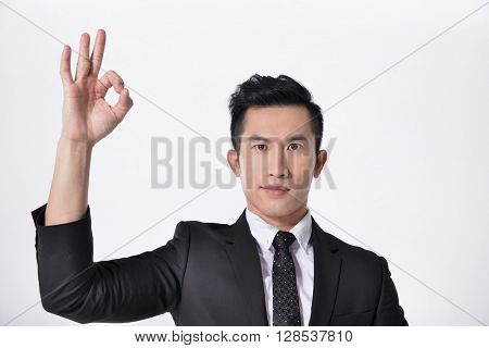 Isolated young business man in suit with ok gesture